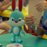 Young children preschoolers having fun with Rabbit Ray's intravenous drip bag role-playing function